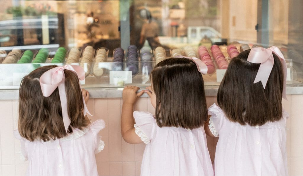 three adorable children pressing their faces against the bakery case trying to decide which delicious treat to get